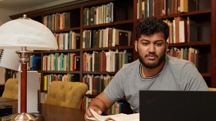 student sitting at desk in a library