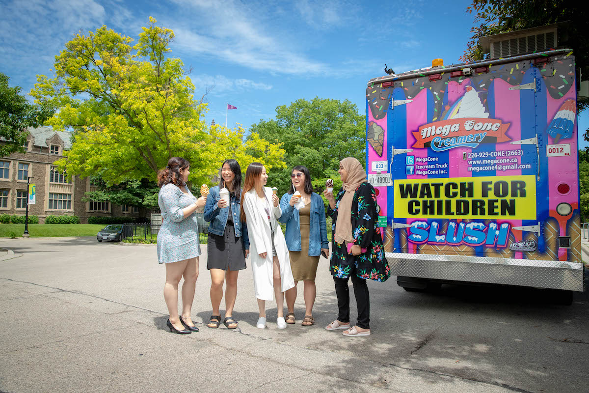 girls standing around enjoying ice cream next to an ice cream truck